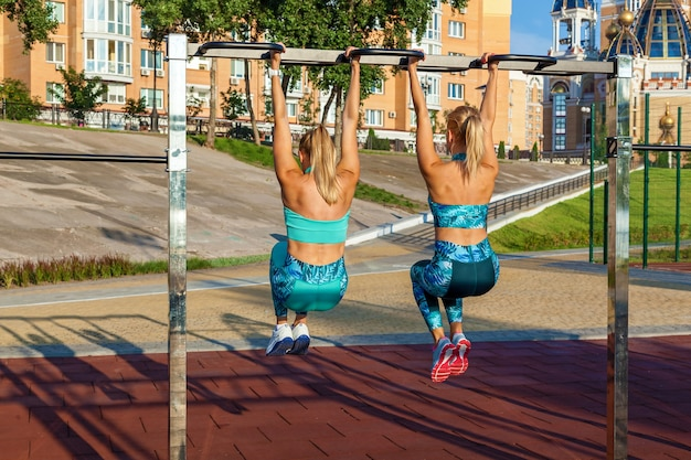 Młode zawodniczki są zaangażowane rano na boisku ćwiczenia fitness