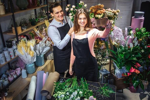 Młode żeńskie i męskie kwiaciarnie stoją w pokoju pełnym kwiatów i roślin. ona trzyma się. robią selfie. ludzie się uśmiechają i pozują.