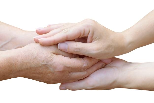Młode żeńskie ręki trzyma stare żeńskie ręki