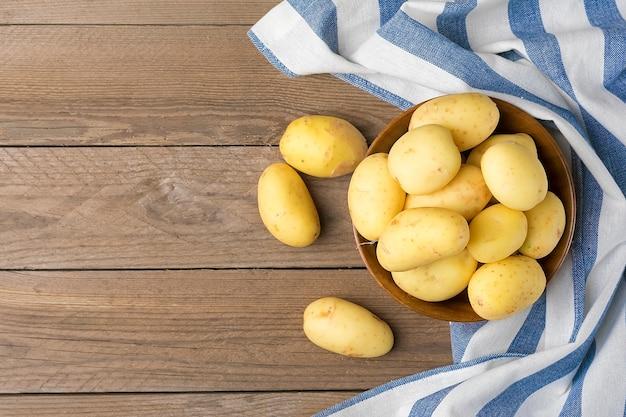 Młode ziemniaki w drewnianej misce, serwetka z niebieskimi i białymi paskami na drewnianym stole. styl rustykalny. widok z góry. leżał płasko.