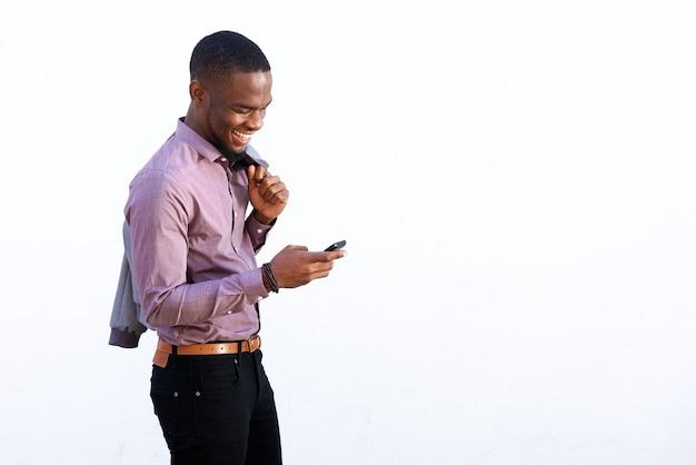 Młodego afrykańskiego faceta czytelnicza wiadomość tekstowa na telefonie komórkowym