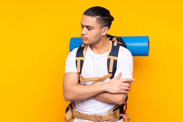 Młodego alpinisty azjatykci mężczyzna myśleć pomysł z dużym plecakiem odizolowywającym na kolor żółty ścianie