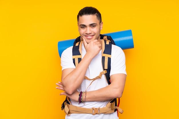 Młodego alpinisty azjatykci mężczyzna z dużym plecakiem na kolor żółty ściany śmiać się