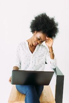 Młodego amerykanina afrykańskiego pochodzenia biznesowa kobieta pisać na maszynie na laptopie podczas gdy siedzący na krześle, odosobnionym na bielu