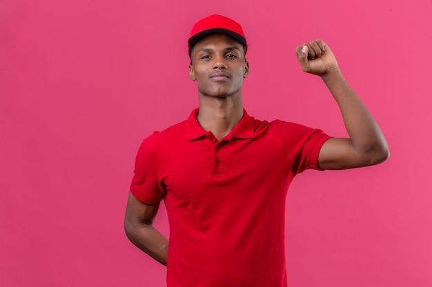Młodego amerykanina afrykańskiego pochodzenia doręczeniowy mężczyzna jest ubranym czerwoną polo koszula i nakrętki pozycję z podnoszenie pięści zwycięzcy pojęciem nad odosobnionymi menchiami