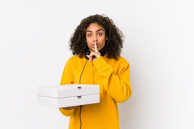 Młodego amerykanina afrykańskiego pochodzenia studencka kobieta trzyma pizze utrzymuje sekret lub pyta o ciszy.