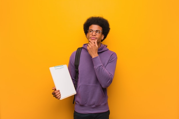 Młodego amerykanina afrykańskiego pochodzenia studencki mężczyzna trzyma schowek wątpi i wprawiać w zakłopotanie