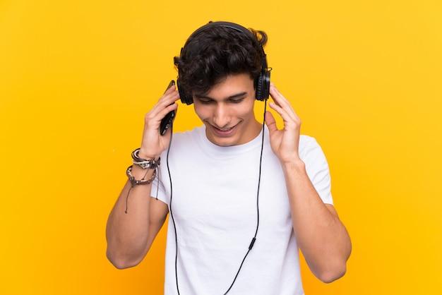 Młodego argentyńskiego mężczyzna słuchająca muzyka z wiszącą ozdobą nad odosobnioną kolor żółty ścianą