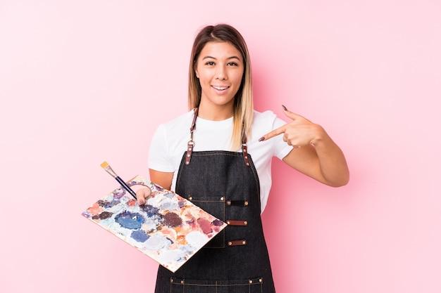 Młodego artysty caucasian kobieta trzyma paletę odizolowywał osoby wskazuje ręcznie koszulowej kopii przestrzeń, dumny i ufny