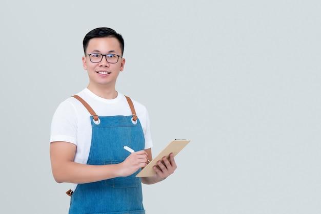Młodego azjatyckiego mężczyzna początkowy właściciel biznesu jest ubranym fartucha bierze rozkaz w schowku