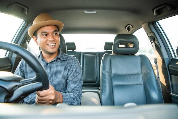 Młodego azjatykciego mężczyzna smiley napędowy samochód.