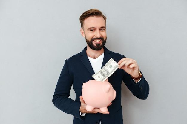 Młodego brodatego mężczyzna przyglądająca kamera podczas gdy stawiać pieniądze w skarbonce