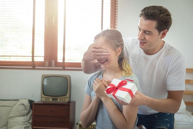 Młodego caucasian chłopaka zaskakująca dziewczyna z prezentem na łóżku. mężczyzna zakrywa oczy dziewczyna i stoi behind, urodziny, gratulacje lub walentynki pojęcie z kopii przestrzenią.
