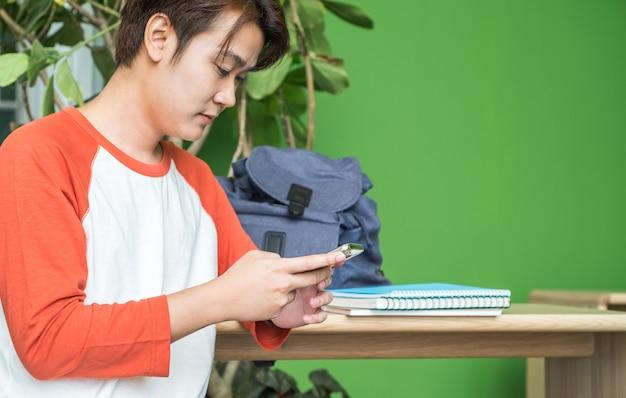 Młodego człowieka azjatykci nastolatek używa telefon komórkowego gawędzi po klasy