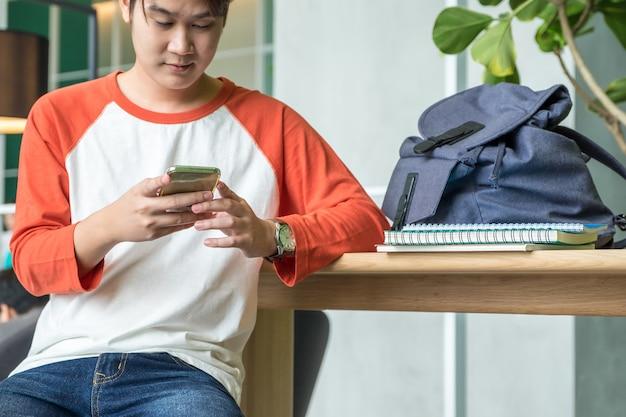 Młodego człowieka azjatykci nastolatek używa telefon komórkowego gawędzi z przyjaciółmi