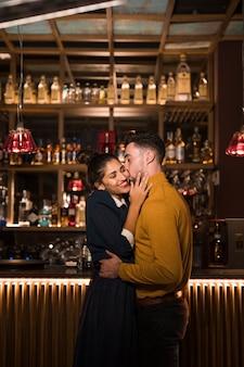 Młodego człowieka całowanie i przytulenie z pozytywną kobietą blisko zakazują kontuar