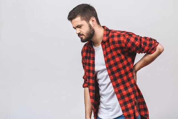 Młodego człowieka cierpienie od bólu pleców odizolowywającego na białym tle. koncepcja bólu pleców.