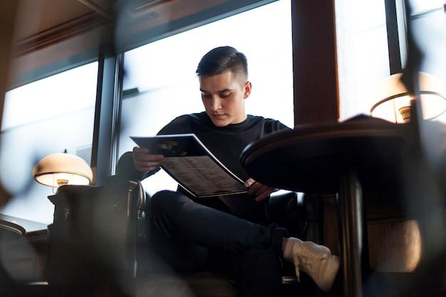 Młodego człowieka czytelniczy menu w kawiarni
