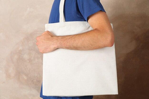 Młodego człowieka mienia dużego ciężaru torba przeciw brown tłu