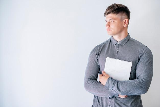 Młodego człowieka mienia notatnik w studiu
