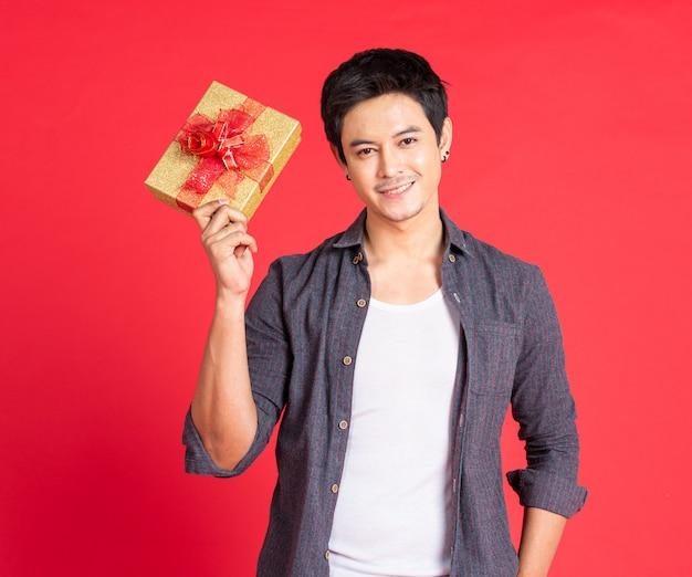 Młodego człowieka mienia prezenta pudełko na czerwieni ścianie