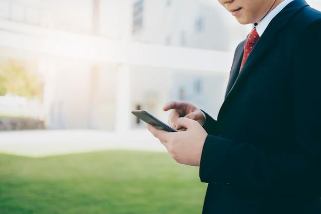 Młodego człowieka mienia smartphone dla biznesowej pracy.