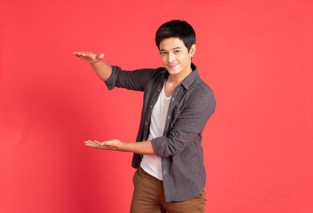 Młodego człowieka mile widziany ręka na czerwieni ścianie