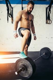 Młodego człowieka narządzanie dla sztangi treningu w gym. położył nogę na sztangi