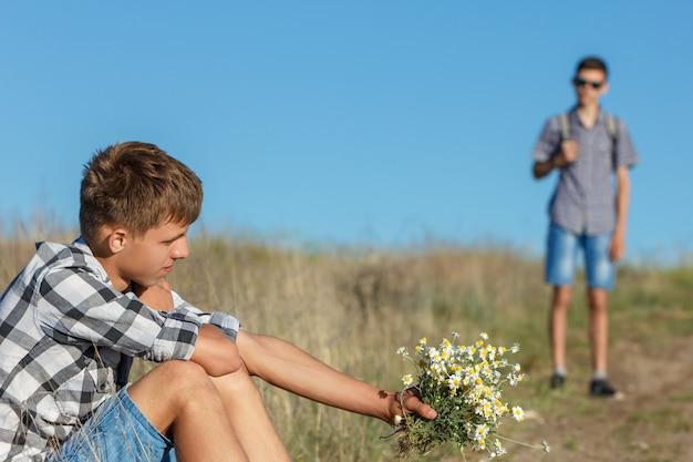 Młodego człowieka obsiadanie drogą z kwiatami