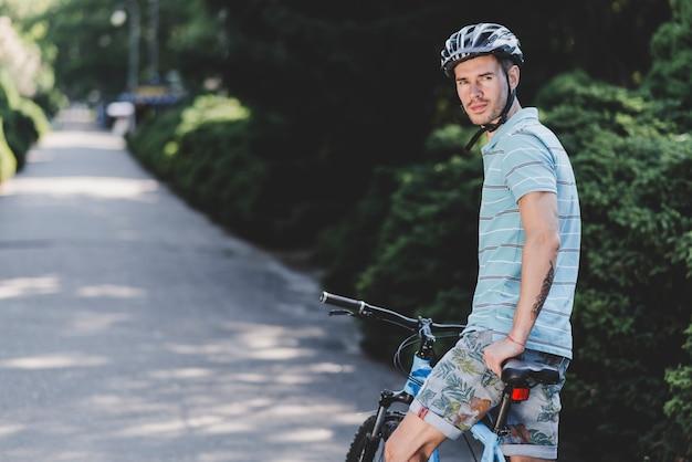 Młodego człowieka obsiadanie na bicyklu jest ubranym ochronnego hełm