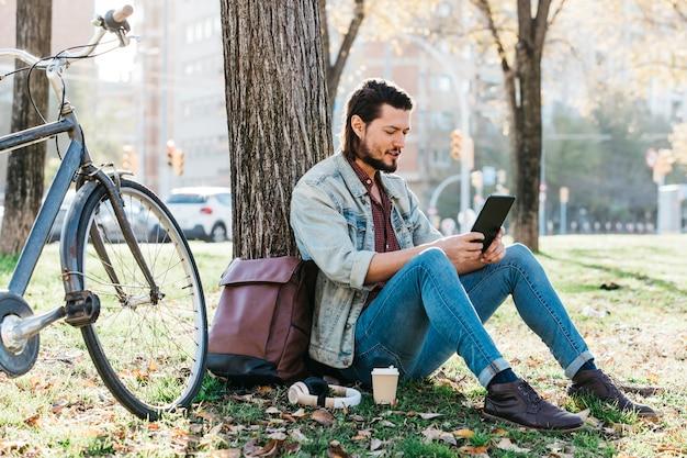 Młodego człowieka obsiadanie pod drzewnym używa telefonem komórkowym w parku z takeaway kawową papierową filiżanką