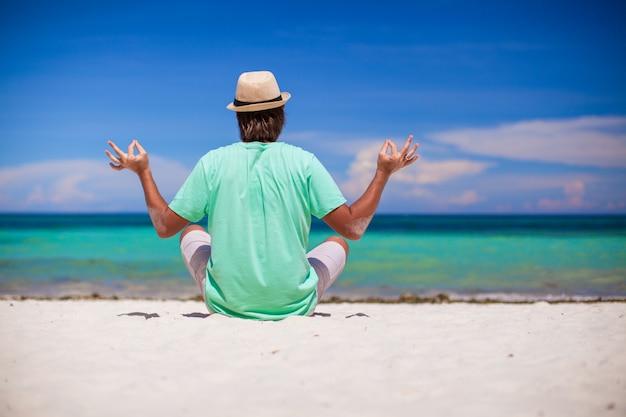 Młodego człowieka obsiadanie w lotosowej pozyci na białej piasek plaży