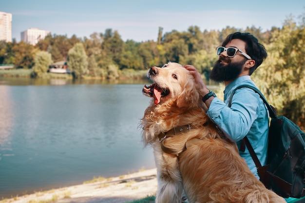 Młodego człowieka obsiadanie z jego psem na krześle w parku