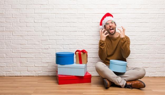 Młodego człowieka obsiadanie z prezentami świętuje boże narodzenia gniewnymi i wzburzonymi