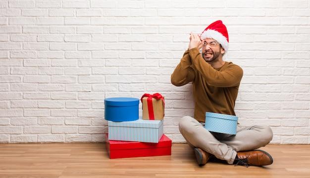 Młodego człowieka obsiadanie z prezentami świętuje boże narodzenia robi gestowi spyglass