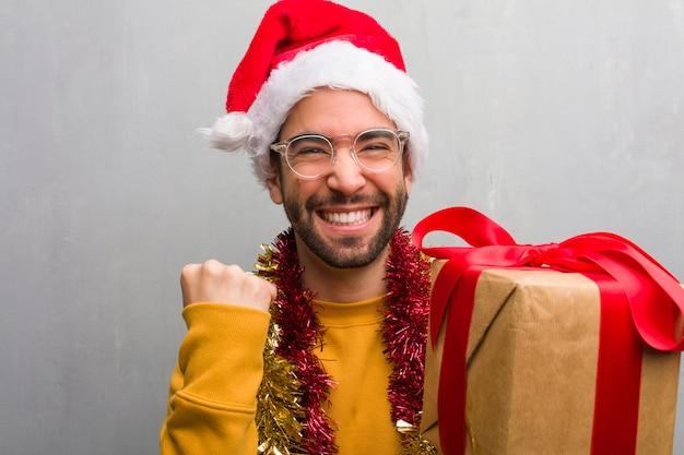 Młodego człowieka obsiadanie z prezentami świętuje boże narodzenia zaskakującymi i szokującymi