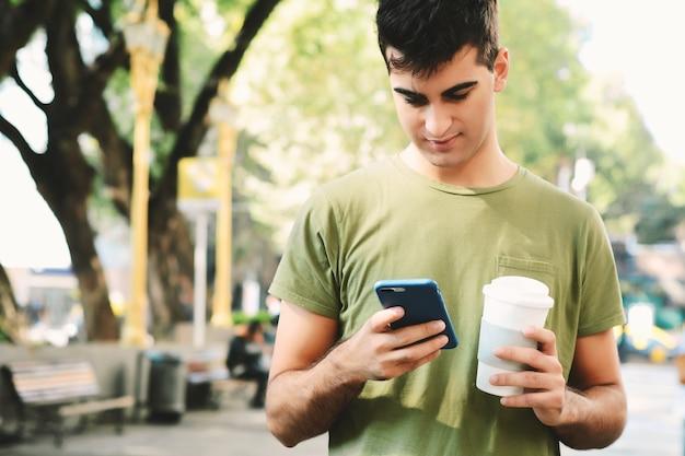 Młodego człowieka pisać na maszynie wiadomość z telefonem komórkowym