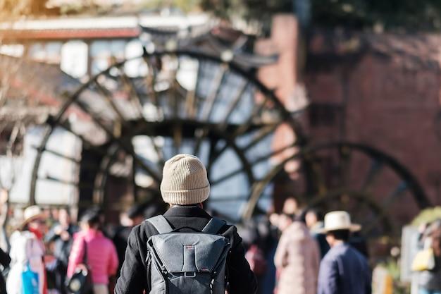 Młodego człowieka podróżnik podróżuje przy gigantycznymi wodnymi kołami w lijiang starym miasteczku, punkcie zwrotnym i popularnym punkcie dla turystów przyciągań w lijiang, yunnan, chiny. koncepcja podróży azji