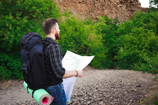 Młodego człowieka podróżnik z mapa plecaka relaksować plenerowy