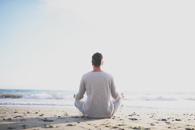 Młodego człowieka praktyki joga na plaży przy zmierzchem.