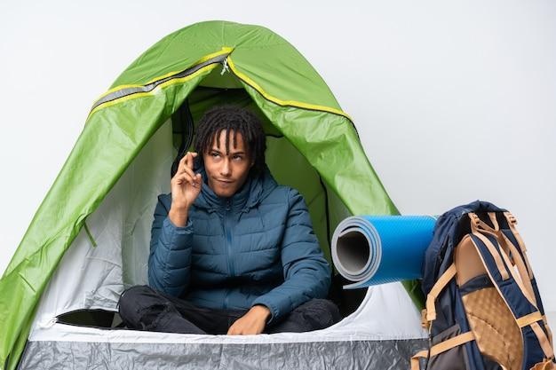 Młodego człowieka sleepeng w campingu nad odosobnioną ścianą