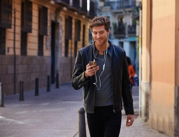 Młodego człowieka słuchające muzyczne smartphone słuchawki