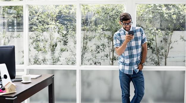 Młodego człowieka spotkanie w firmie przez rozmowę wideo ze smartfonem w domu.
