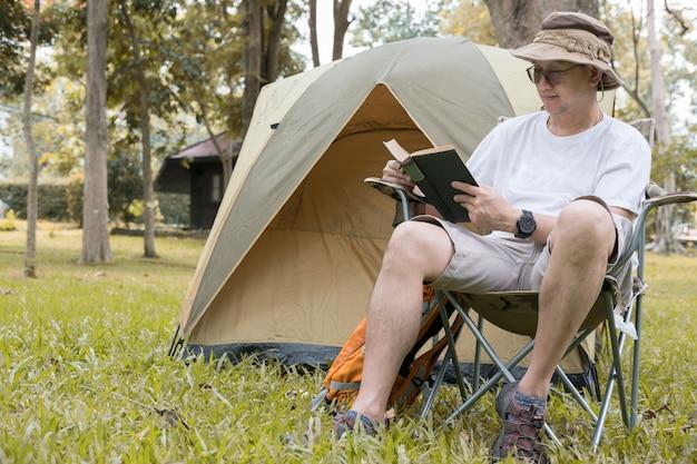 Młodego człowieka turystyczny obsiadanie na krześle i czytelniczej książce przed namiotem przy campingiem w lesie.