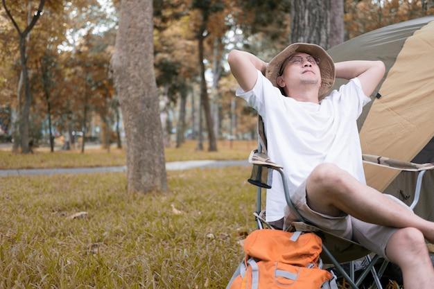 Młodego człowieka turystyczny obsiadanie na krześle odpoczywa i relaksuje przed namiotem przy campingiem w lesie