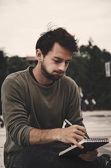 Młodego człowieka writing w notatniku przy naturą, boczny widok. profil brodaty mężczyzna rysunek