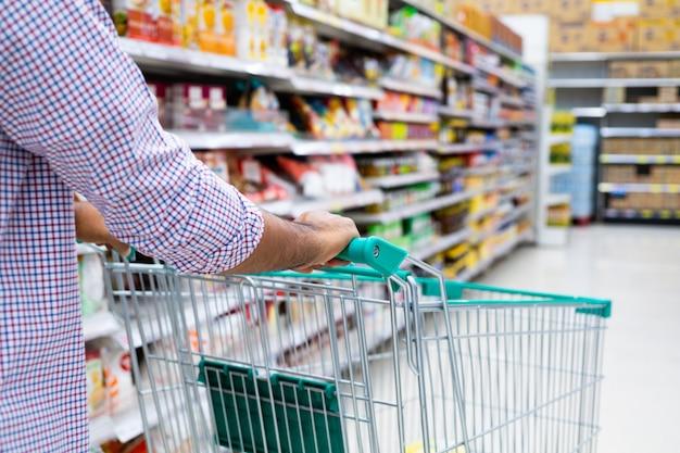 Młodego człowieka zakupy przy supermarketem.
