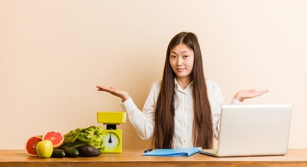 Młodego dietetyka chińska kobieta pracuje z jej laptopem wątpi i wzrusza ramionami on ramiona w przesłuchanie gescie.