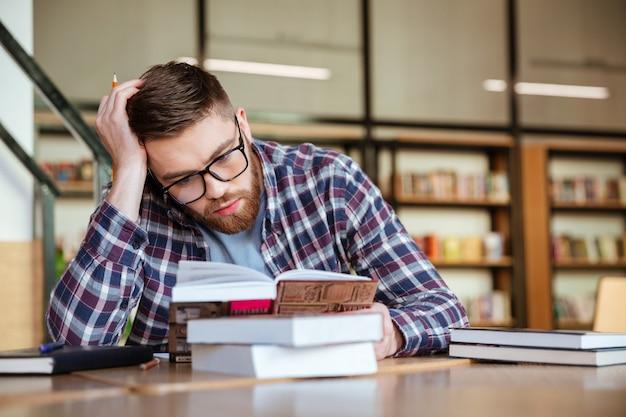 Młodego faceta studencka czytelnicza książka z poważną twarzą
