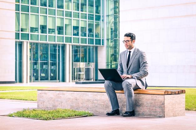 Młodego modnisia biznesowego mężczyzna obsiadanie z laptopem przy centrum biznesu